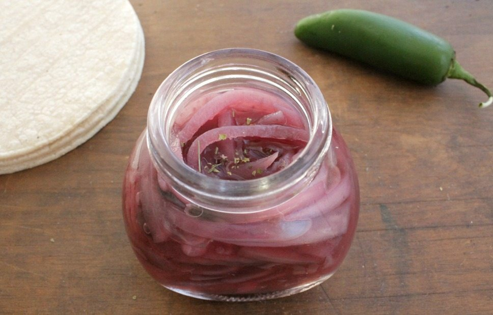 Mexican Pickled Onions in a jar on a wooden surface next to a jalapeno pepper and tortillas.