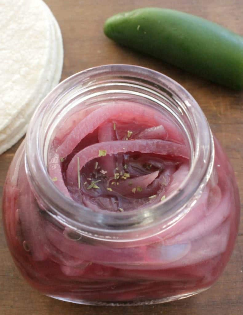 Mexican Pickled Red Onions (Cebolla Morada en Escabeche) in a jar next to a jalapeno pepper and stack of tortillas.