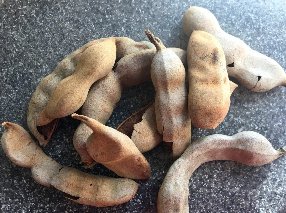 Tamarind pods piled on a cutting board.