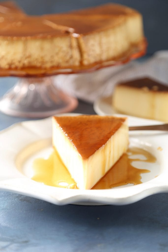 A slice of flan sitting on a white plate next to a cake stand with the entire dessert.
