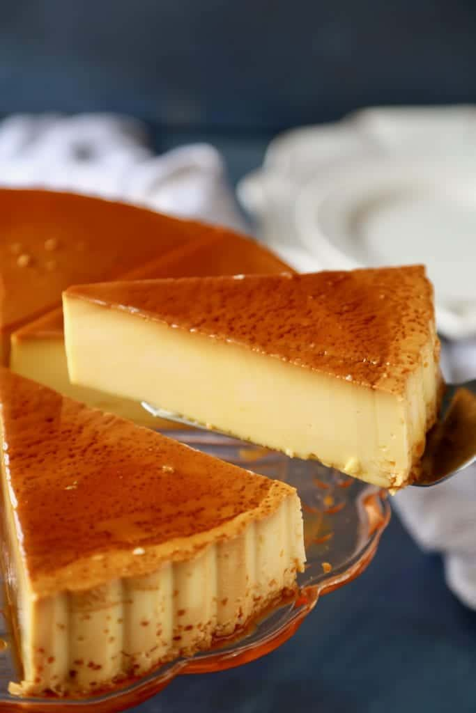 A cake knife removing a slice of Flan from the dessert.