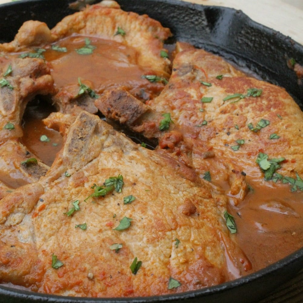 Pork Chops in Mexican Red Salsa, or Chuletas en Salsa Roja, in a cast iron skillet topped with chopped cilantro. By Mama Maggie's Kitchen