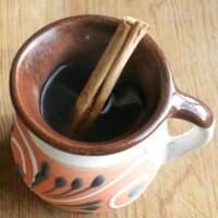 Café de la Olla in a decorative Mexican cup with a cinnamon stick.