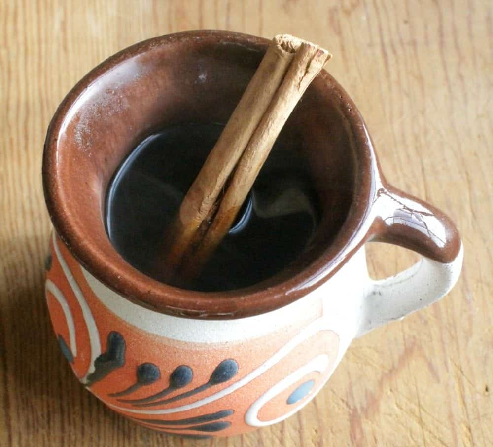 Café de la Olla in a decorative Mexican cup with a cinnamon stick.