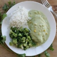Chicken in Creamy Poblano Sauce on a white plate topped with corn kernels and surrounded by rice and broccoli.