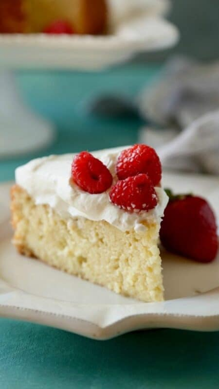A slice of Tres Leches Cake on a white plate topped with raspberries.