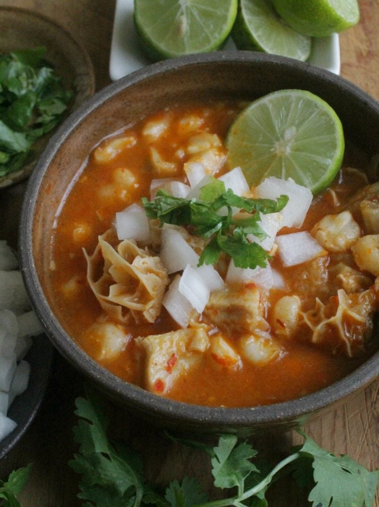 Menudo, or Pancita, in a brown bowl topped with lime, cilantro, and chopped onions.