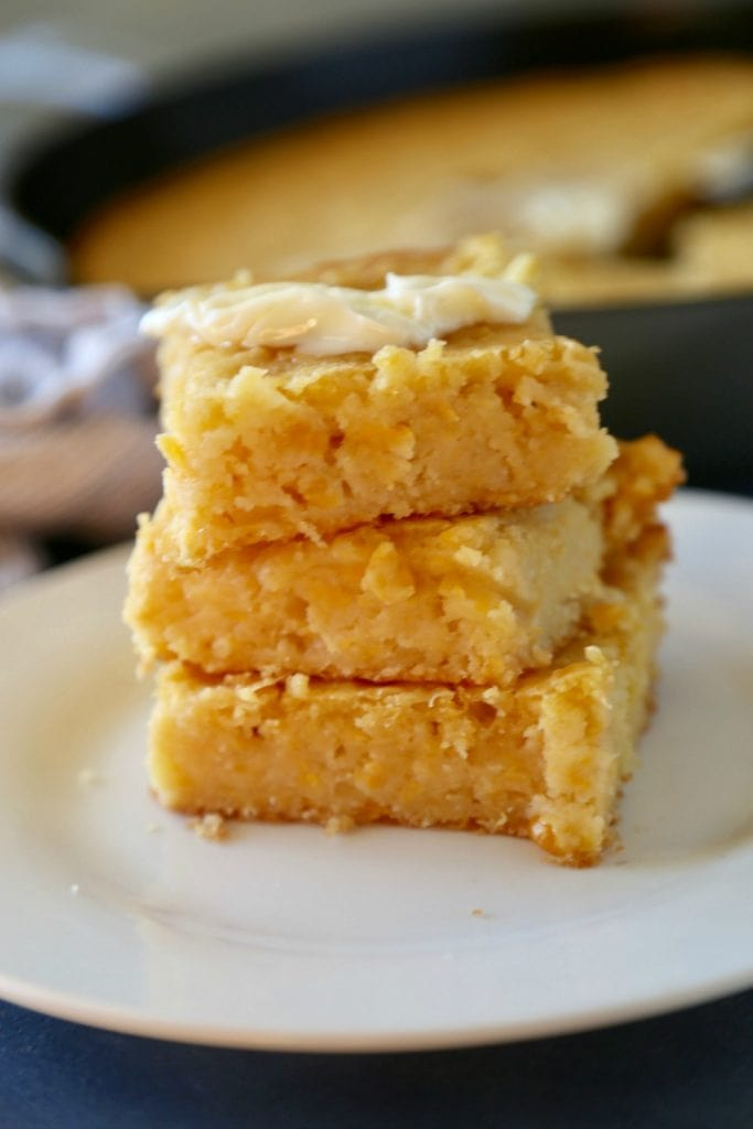 Pieces of Pan de Elote, or Mexican Sweet Corn Cake, stacked on top of a white plate and topped with a tab of butter.