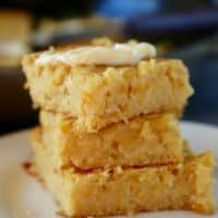 Pan de elote stacked on a white plate and topped with a dab of butter.