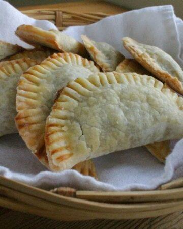 Empanadas de Calabaza in basket on top of a white towel.