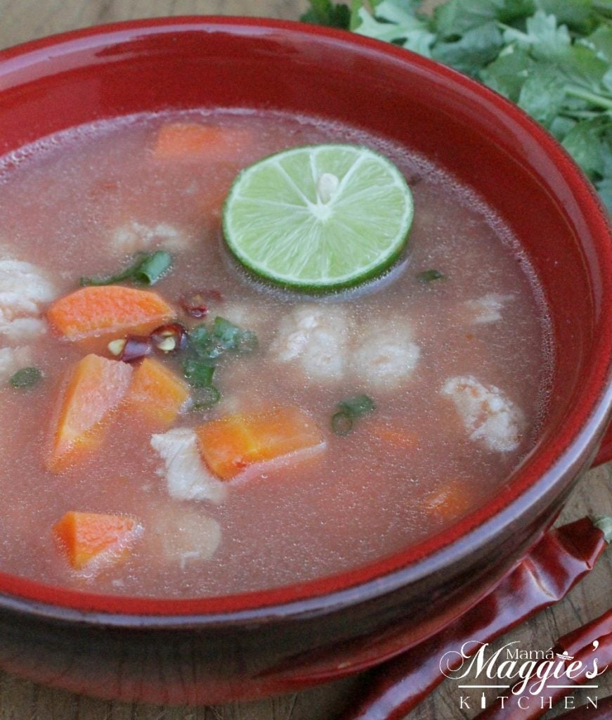 Caldo de Pescado in a red bowl with veggies and lime wedges.