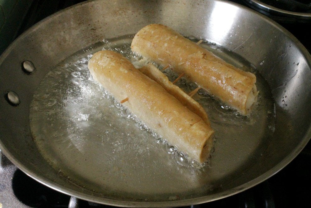 Taquitos frying in oil in a metal pan