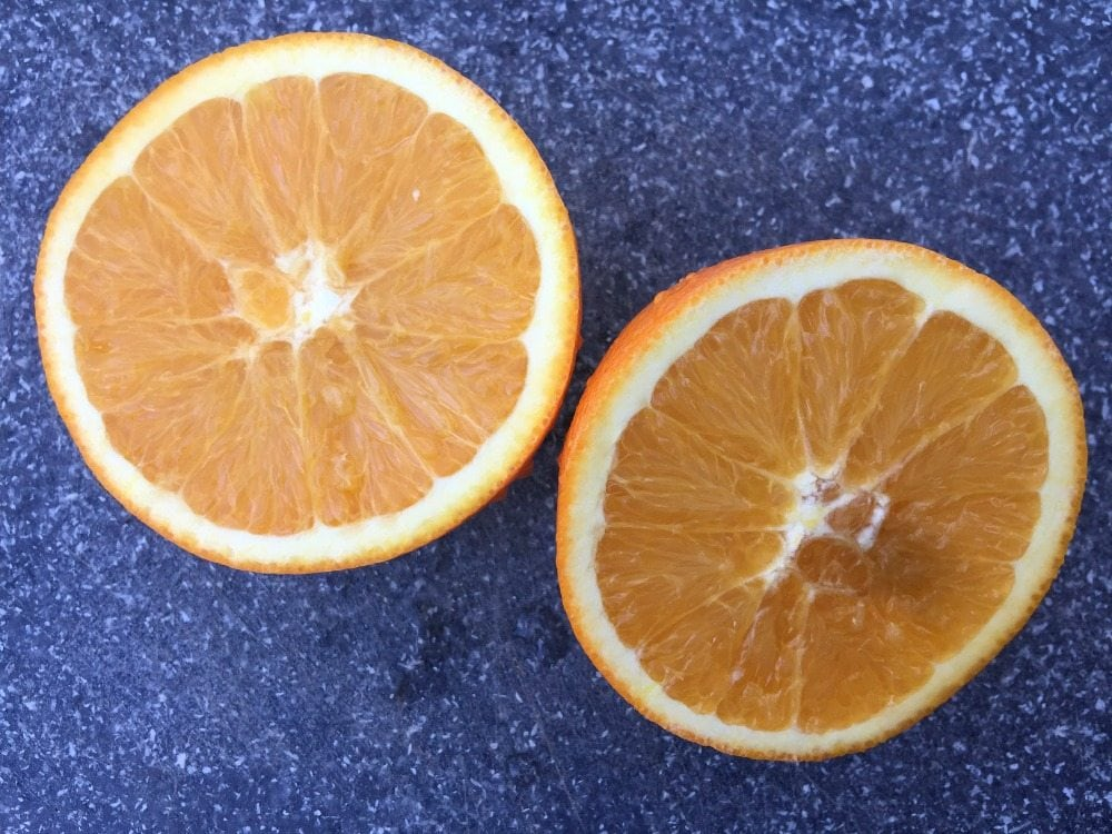 Oranges cut in half on a cutting board.