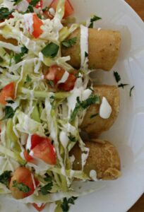 Potato and Cheese Taquitos topped with shredded cabbage, diced tomatoes, chopped cilantro, and Mexican crema