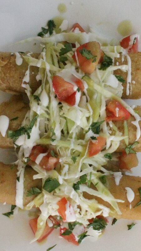 Taquitos on a white plate topped with shredded cabbage diced tomatoes chopped cilantro and drizzled with Mexican cream sauce