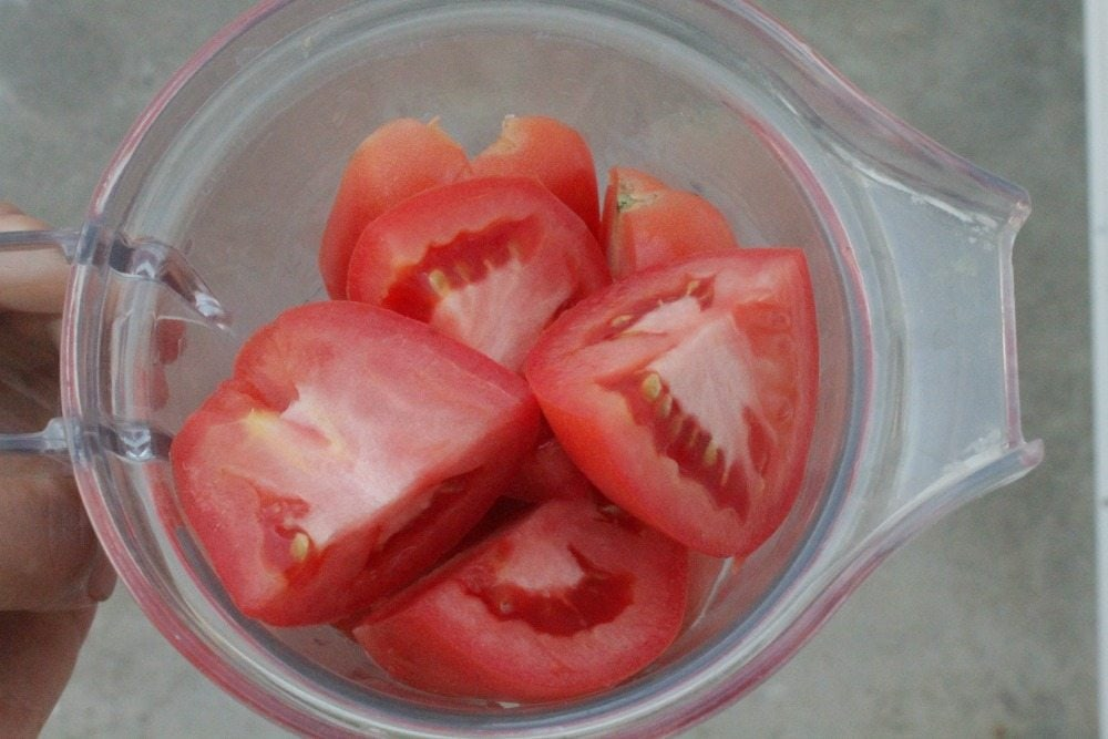 Tomatoes cut in quarters in a blender.