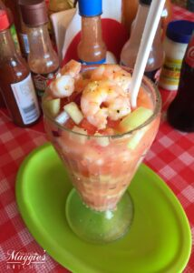 Coctel de Camarones (Mexican Shrimp Cocktail) in a glass on a green plate and red checkered tablecloth.