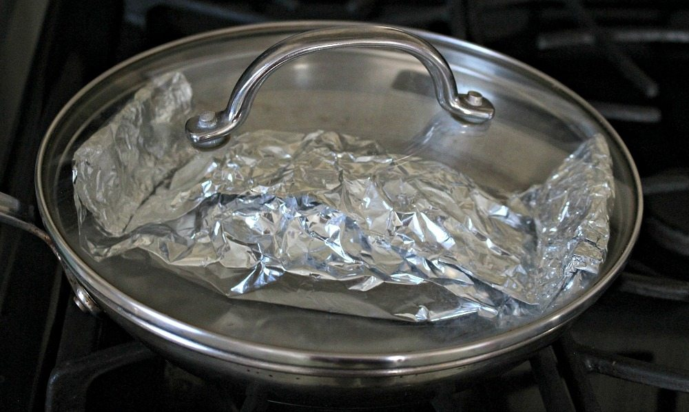 Foil packet inside a skillet with lid on