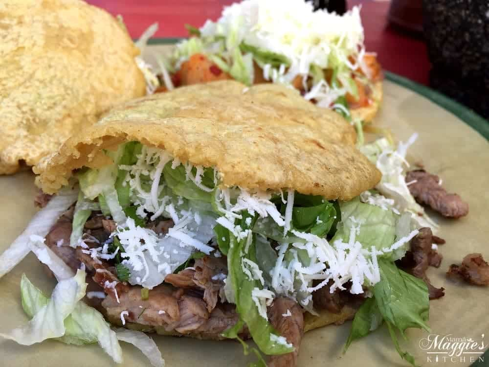 Gorditas cut open in half and stuffed with carne asada lettuce and cheese.