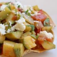Mexican Calabacitas Recipe, or Calabacitas a la Mexicana, on a tostada and topped with queso fresco.