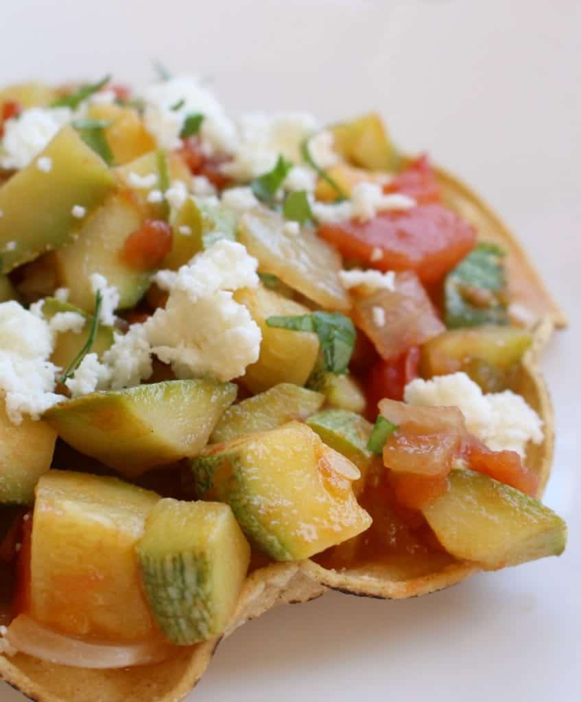 Mexican Calabacitas Recipe, or Calabacitas a la Mexicana, on a tostada and topped with queso fresco.