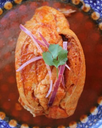 Torta Ahogada, or Drowned Sandwich, topped with pickled red onions and a cilantro leaf, surrounded by a spicy tomato sauce on a blue plate.