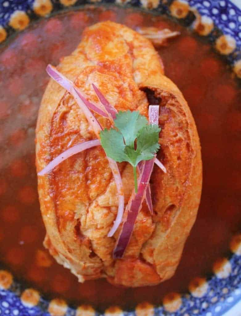 Torta Ahogada, or Drowned Sandwich, topped with pickled red onions and a cilantro leaf, surrounded by a spicy tomato sauce on a blue plate