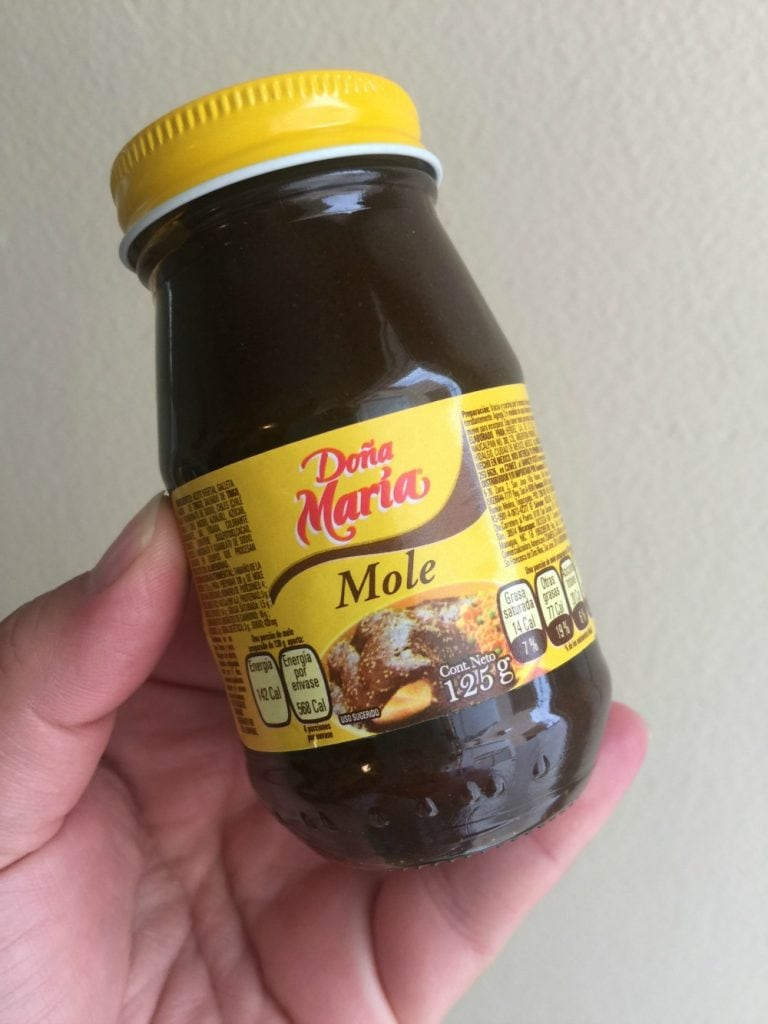 Hand holding a container of Dona Maria Mole.