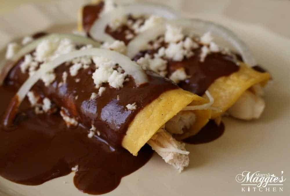 Enmoladas covered in a savory mole sauce and topped with queso fresco and slices of white onion.