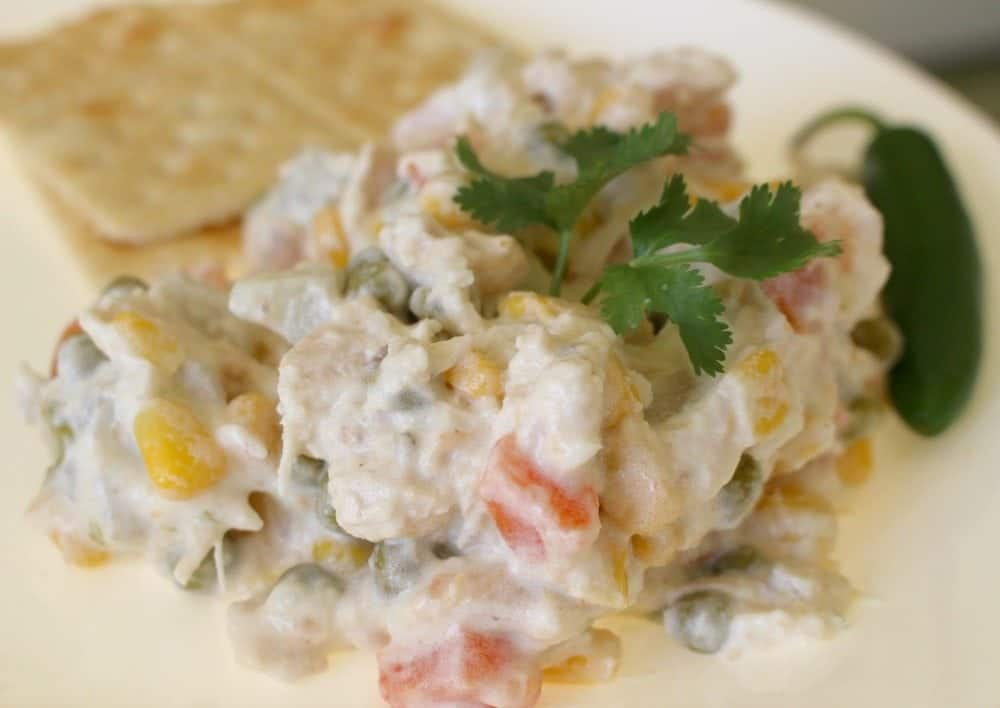 Ensalada de Pollo, or Mexican Chicken Salad, topped with cilantro leaf saltine cracker and jalapeno
