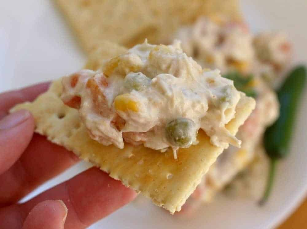 Hand holding saltine cracker topped with Mexican Chicken Salad, or Ensalada de Pollo