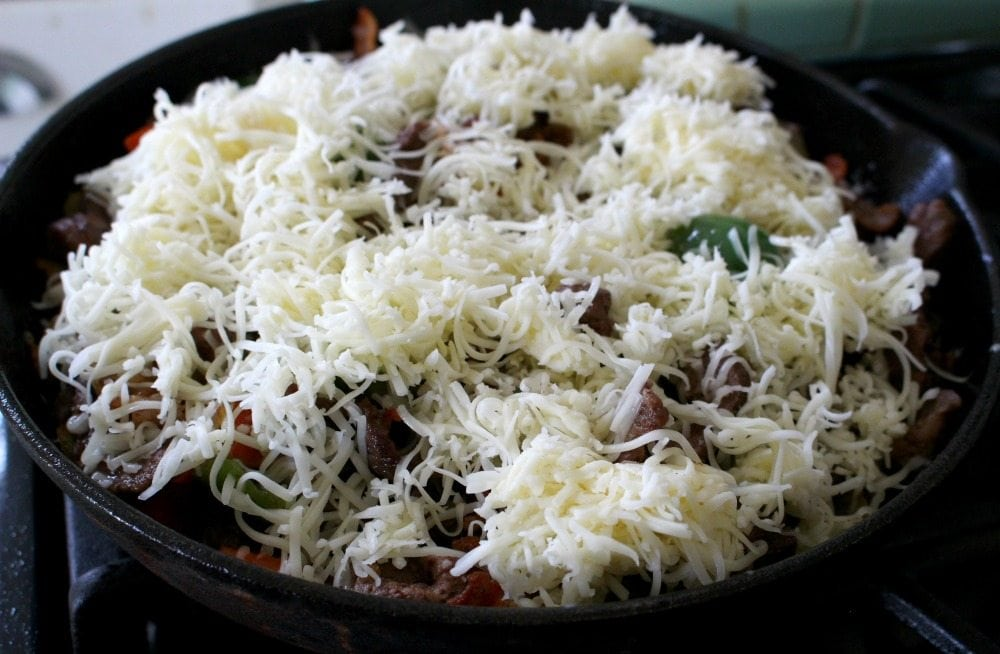 Shredded white cheese on top of alambres in a black skillet