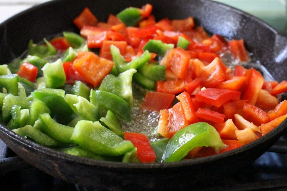 green and red peppers in black cast iron skillet