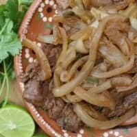 Bistec Encebollado, or Mexican-Style Beef and Onions, lime wedges cilantro on Mexican clay plate
