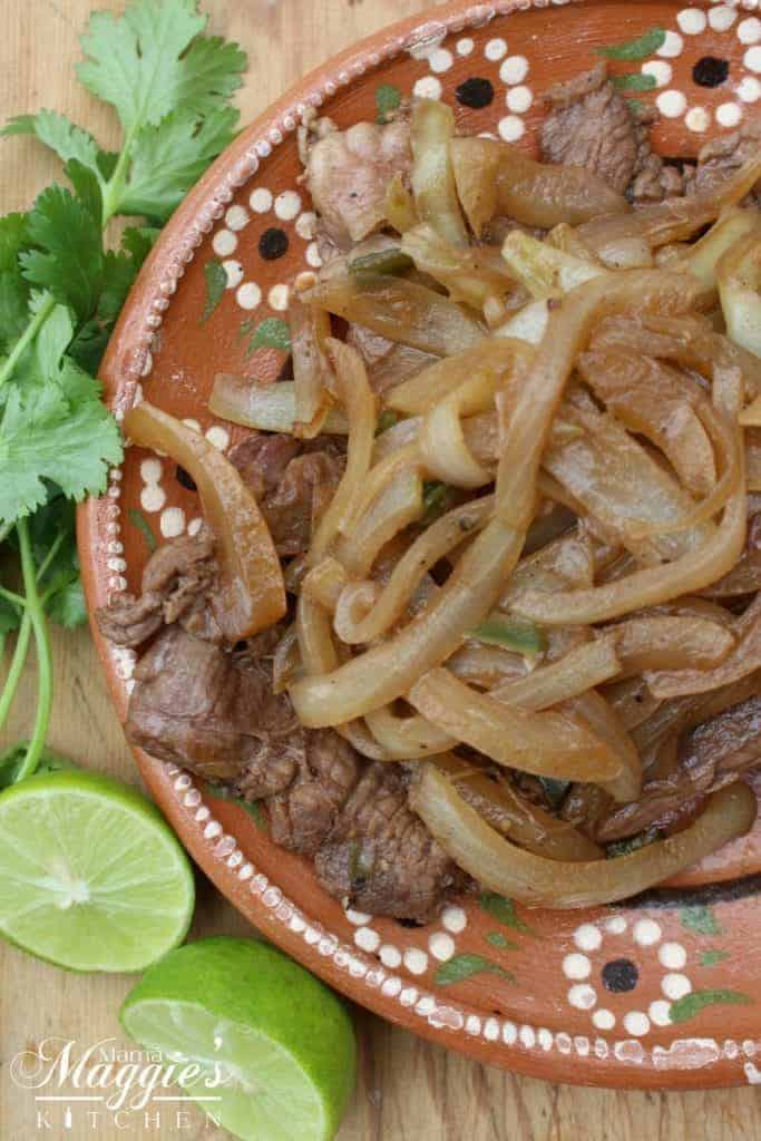 Bistec Encebollado, or Mexican-Style Steak and Onions, lime wedges cilantro on Mexican clay plate