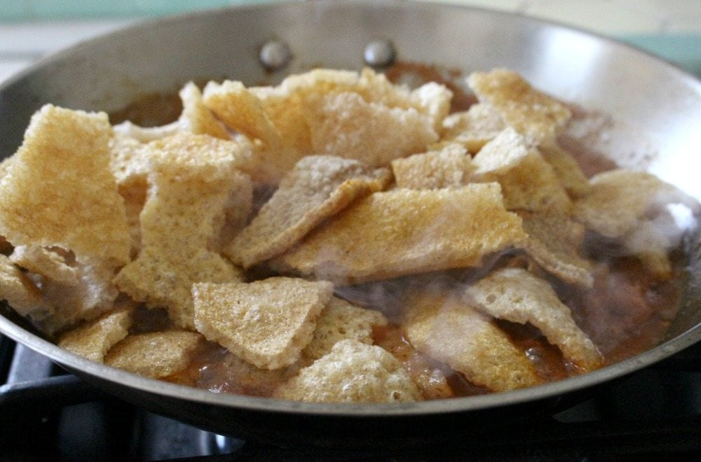 Pieces of Pork Cracklings in a skillet over tomato mixture