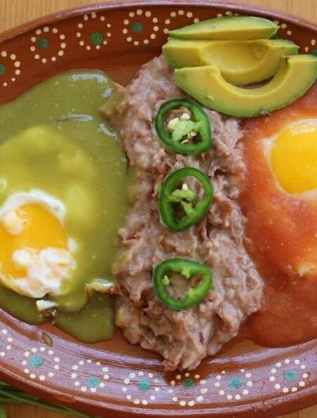 Divorced Eggs or Huevos Divorciados on a decorative Mexican terra cotta clay plate