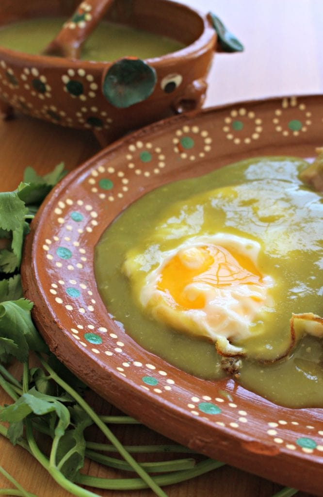 Egg covered in green salsa in a Mexican terra cotta plate