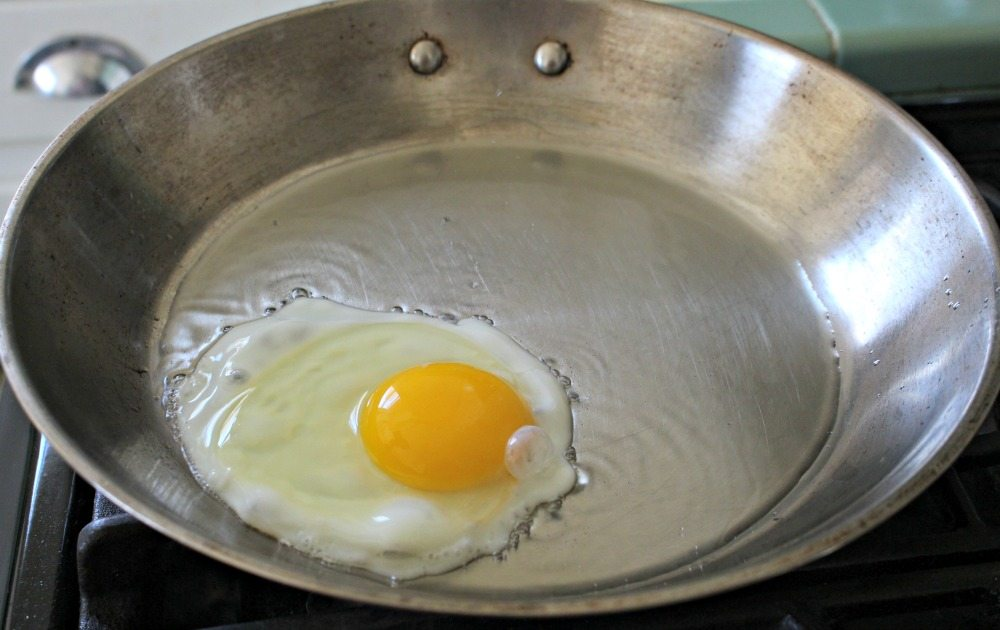 Egg frying in metal skillet