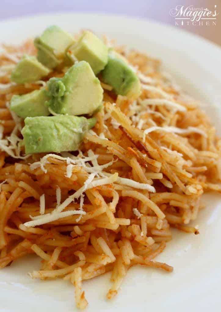 Fideo Seco, or Mexican Pasta, topped with diced avocado and shredded cheese