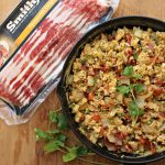 Smithfield bacon package with eggs inside cast iron skillet topped with cilantro