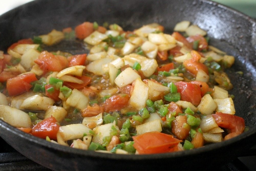 Tomato, onions, and jalapenos cooking in a cast iron skillet