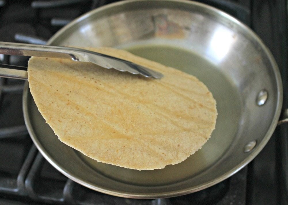 Tongs holding tortilla over metal skillet