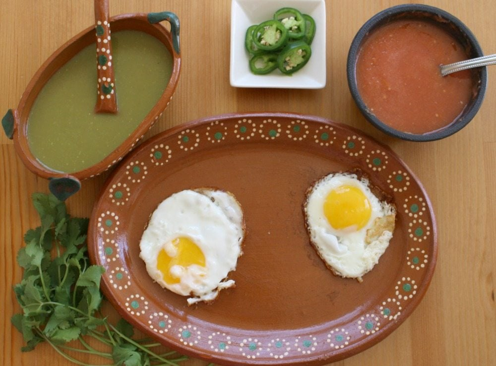 Two Eggs Green and Red Salsa jalapeno slices on a decorative Mexican terra cotta plate