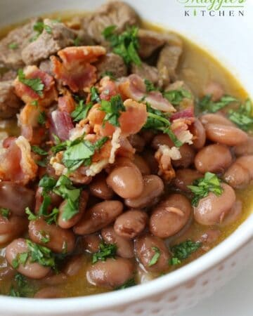 Carne En Su Jugo in a white bowl topped with cilantro beans bacon