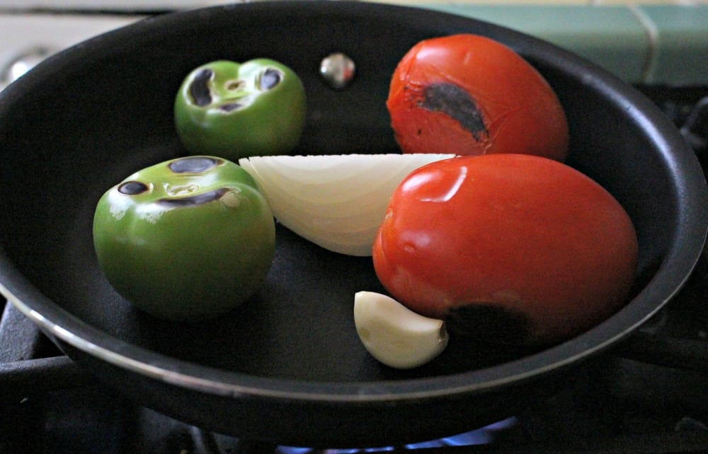 Tomatoes, tomatillos, garlic, and onion in a skillet.