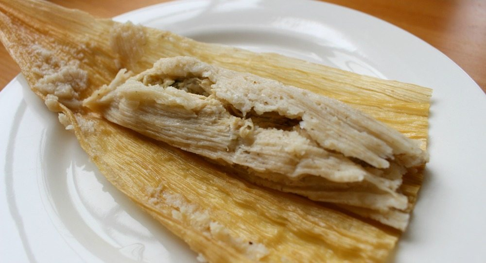 Chicken Tamale in an opened corn husk on white plate
