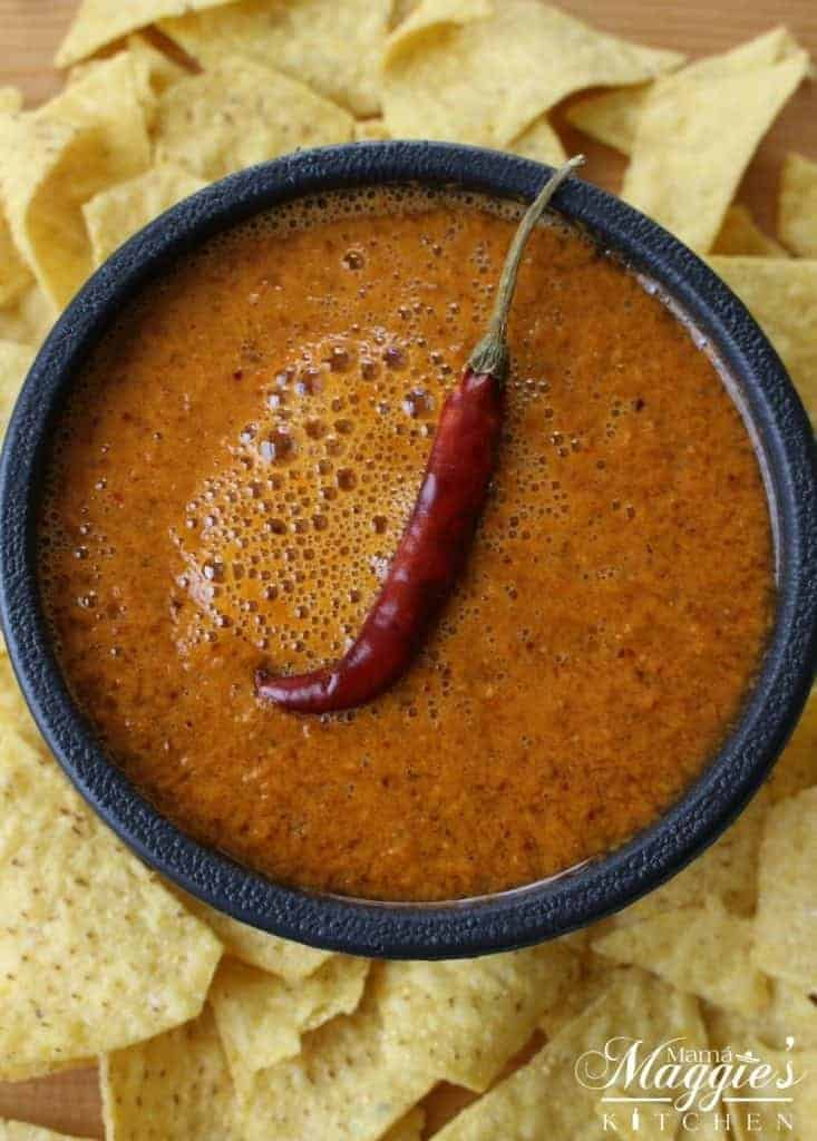 Bowl of Chile de Arbol Salsa surrounded by chips and topped with a single dried chile pod.