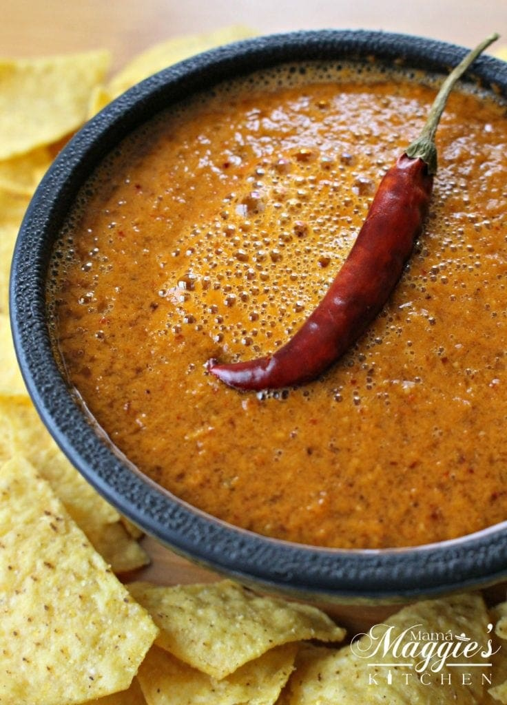 Bowl of Chile de Arbol Salsa surrounded by chips and topped with a single dried chile.