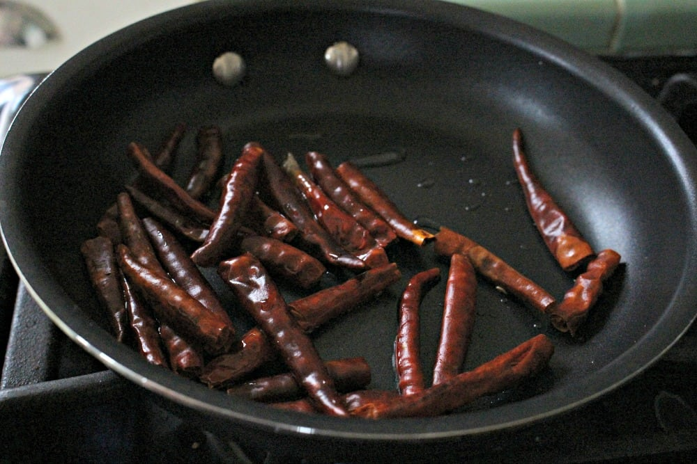 Chile de Arbol pods cooking in a skillet.